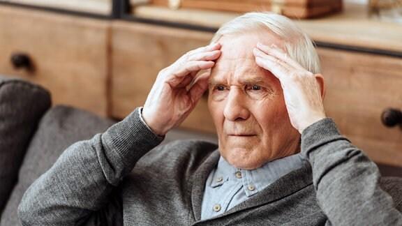 grauhaariger Mann greift sich mit beiden Händen an den Kopf