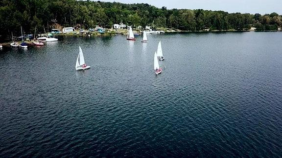 Mehrere Segelboote auf einem See, im Hintergrund am Ufer die Anlegestellen und der Campingplatz.
