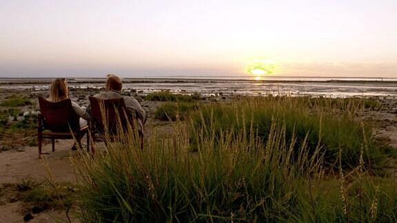 Eine Frau und ein Mann sitzen in Stühlen am Meer und genießen den Sonnenuntergang.