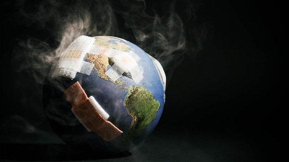 Modell einer Erde dampft und ist mit Pflastern beklebt