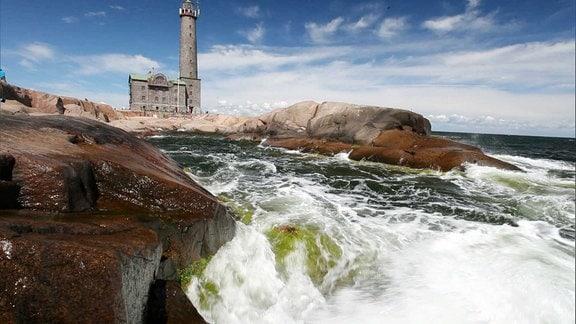 Gischt schäumt am Ufer, im Hintergrund steht ein Leuchtturm