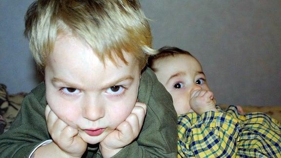 Ein kleiner Junge schaut wütend in die Kamera. Hinter ihm nuckelt sein jüngeres Geschwisterchen am Daumen.
