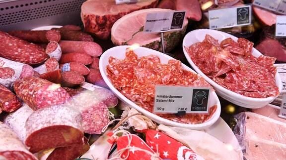 Salami und Schinken liegen in der Auslage einer Metzgerei
