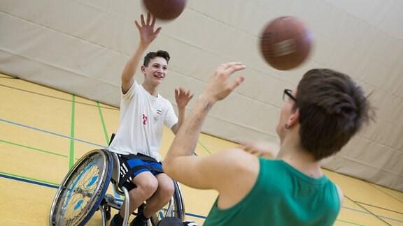 Zwei Jugendlich im rollstuhl spielen Basketball.