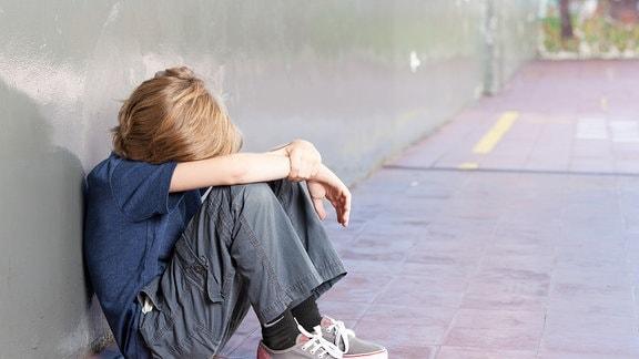 Junge sitzt traurig an einer Wand und vergräbt sein Gesicht im Schoß