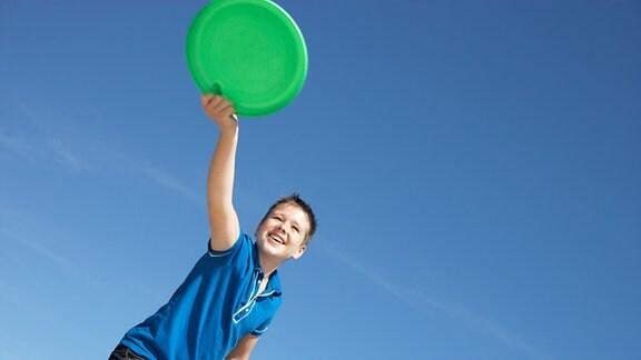 Ein Junge wirft eine grüne Frisbeescheibe.