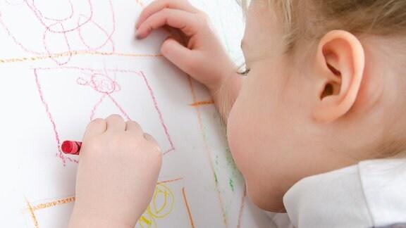 Ein kleines Mädchen malt mit der linken Hand ein Bild.