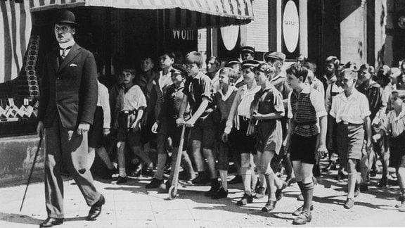 Hunderte Jungen verfolgen den Verbrecher (Fritz Rasp, l.) durch die Straߟen Berlins und treiben ihn in die Enge.