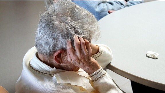 Eine von hinten oben zu sehende alte Frau sitzt an einem Tisch und fasst sich mit den Händen an den Kopf