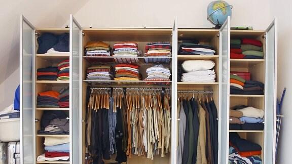 Kleiderschrank eines Mannes. Bekleidung aller Art hängt und liegt in verschiedenen Schrankfächern.