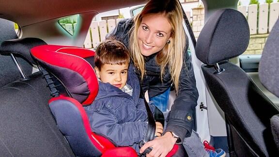 Eine Mutter schnallt ihren Sohnemann im Autokindersitz an.