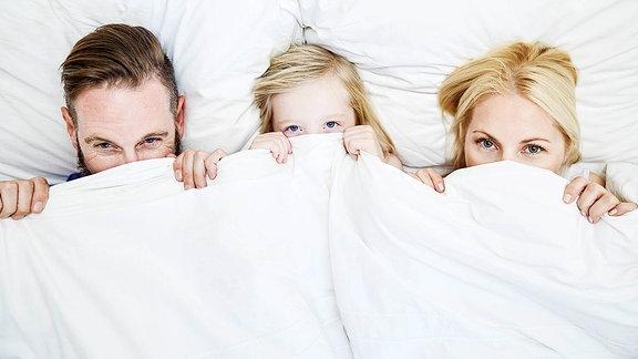 Eine Familie unter der Bettdecke.