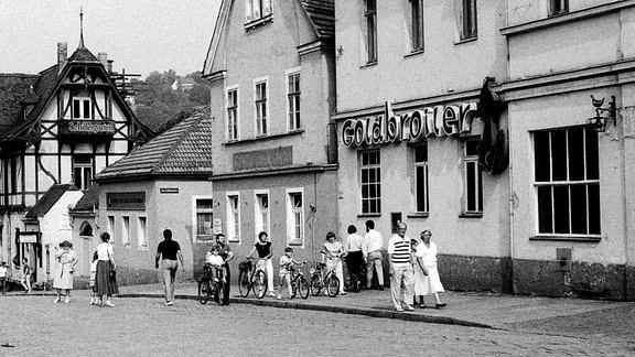 Schwarzweißaufnahme: Menschen vor einem Goldbroiler-Restaurant in Dresden-Blasewitz.