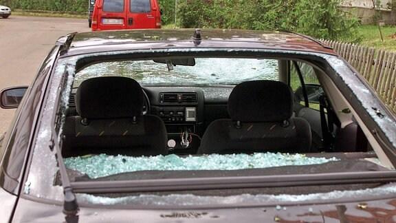 Ein Auto mit Dellen und zerstörten Scheiben nach einem Hagelschauer