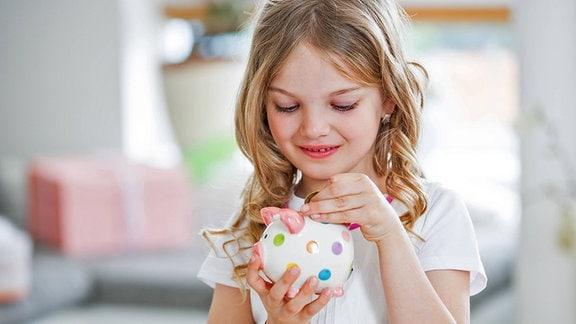 Eine Mädchen steckt eine Münze in ihr Sparschwein