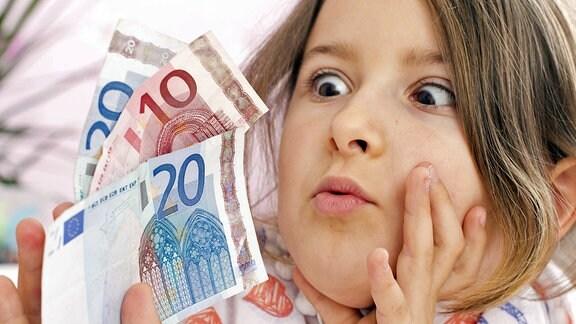 Ein Mädchen schaut erstaunt auf Geldscheine, die es in seiner Hand hält