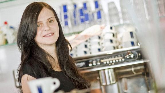 Eine junge Frau hinter einem Tresen in einem Café