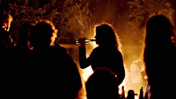 Eine Nachtaufnahme zeigt den Umriss einer jungen Frau, die während einer Party zwischen anderen an einem Lagerfeuer steht und Bier aus der Flasche trinkt