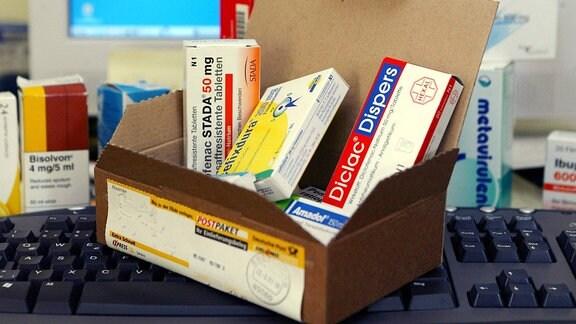Ein geöffnetes Paket mit verschiedenen Medikamenten steht auf einer Computertastatur.