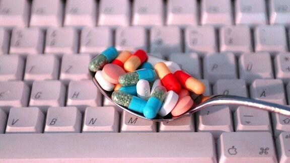 Ein Löffel mit verschiedenfarbigen Medikamenten wird über eine Computertastatur gehalten.