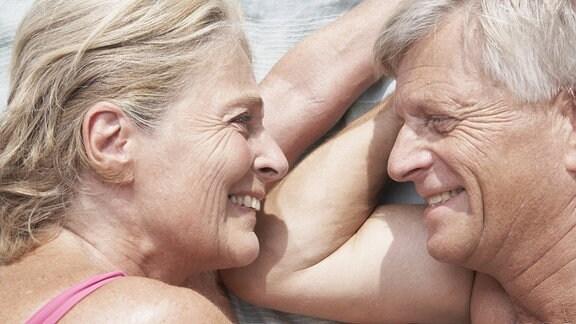 Ein älteres Paar liegt vertraut nebeneinander draußen auf einer Decke.