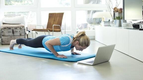 Eine Frau macht auf einer Trainingsmatte Liegestütze. Vor ihr steht ein aufgeklapptes Notebook.