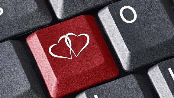 Zwei verschlungene Herzen auf einer roten Taste einer Computer-Tastatur