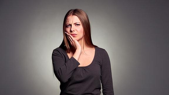 Eine junge Frau hält sich die Wange