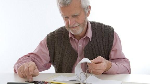 Ein Mann um die 60 sitzt vor einem Ordner mit Kontoauszügen und tippt auf seinem Taschenrechner.