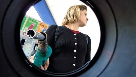 Blick aus dem Tank eines Autos auf eine Frau, die einen Tankpistolel in der Hand hält.