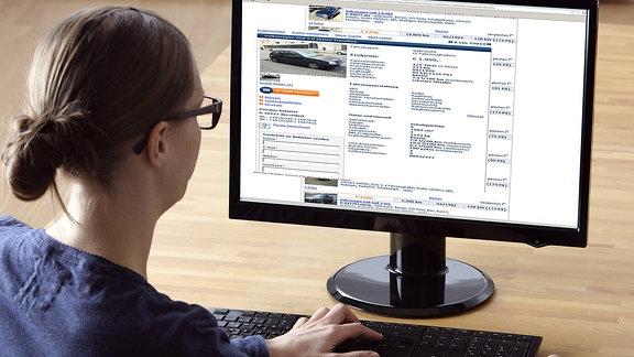 Eine Frau sucht auf einem Online-Portal für Gebrauchtwagen