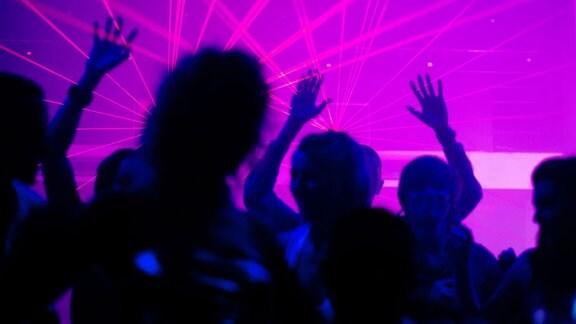 Menschen tanzen vor dem lila reflektierendem Licht einer Diskokugel.