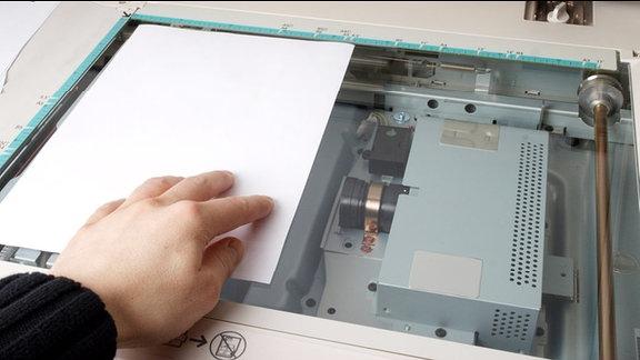 Eine Hand legt eine bedrucktes Blatt Papier auf die Auflage eines Kopierers.