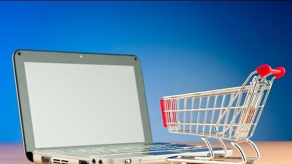Ein Einkaufswagen steht auf der Tastatur eines Laptops.
