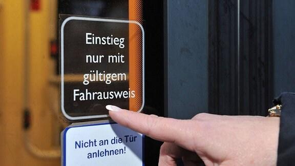 Eine Frau zeigt auf einen Hinweisaufkleber am Fenster einer Straßenbahn mit der Aufschrift Einstieg nur mit gültigem Fahrausweis