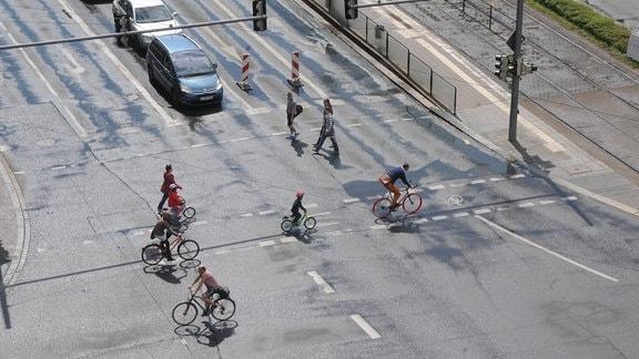 Fahrradfahrer fahren über eine Kreuzung.