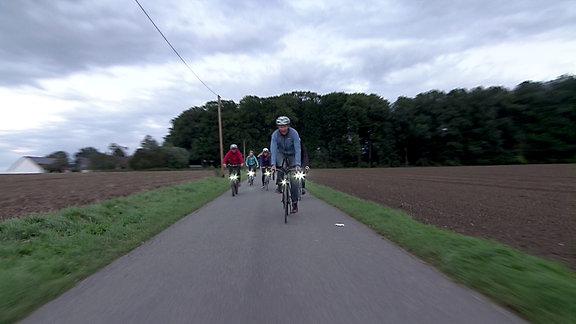 Eine Gruppe von Fahrradfahrern fährt mit eingeschalteter Fahrradbeleuchtung durch die Dämmerung.
