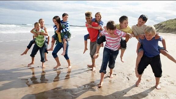 Jugendliche rennen, sich huckepack tragend, einen Strand entlang.
