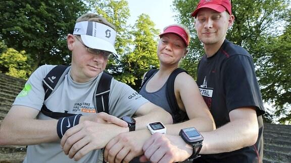 Drei Sportler mit Fitness-Trackern.