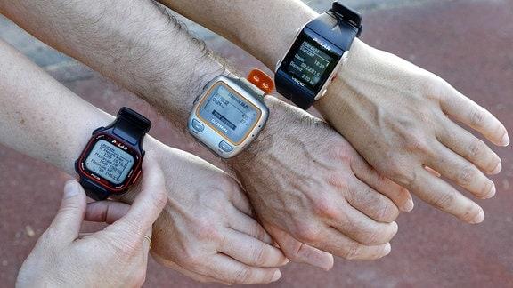 Drei Arme mit Fitness-Trackern.