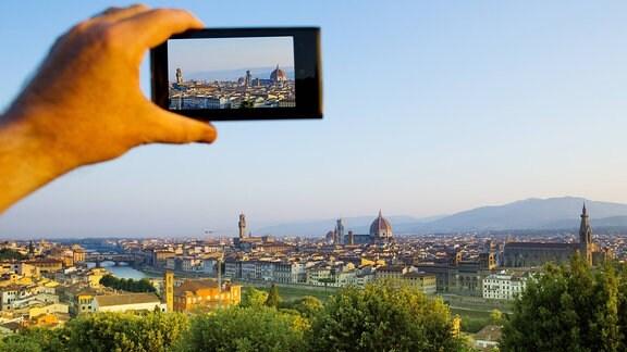 Vor das Panorama von Florenz wird ein Telefon gehalten.