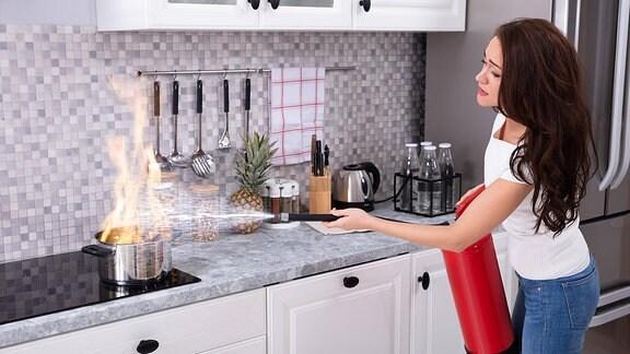 Eine Frau löscht mit einem Feuerlöscher einen brennenden Topf auf einem Herd