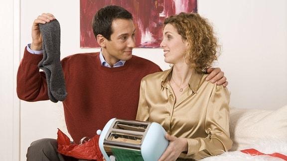 Eine Frau und ein Mann sitzen mit ihren Weihnachtsgeschenken auf dem Sofa und spielen sich Freude vor. Er hält ein paar graue Socken hoch, sie hält auf ihrem Schoß einen Toaster.