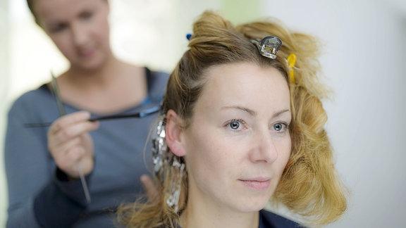 Eine junge Frau lässt sich von einer Friseurin Strähnchen ins Haar machen.