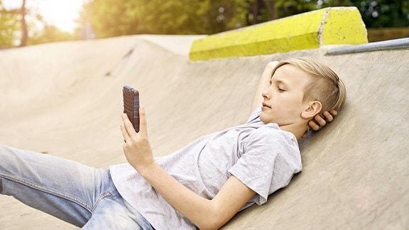 Ein Junge liegt an einer Betonwand und spielt mit seinem Handy