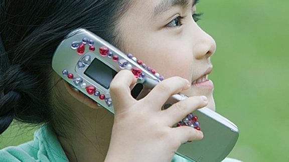 Ein Mädchen telefoniert mit seinem Handy.