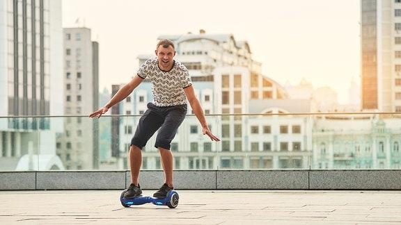 Ein junger man fährt auf einem Hoverboard.