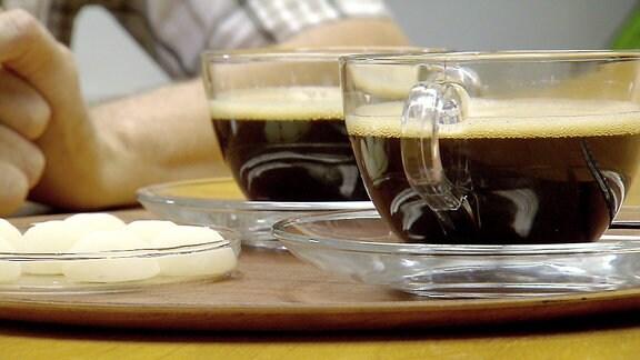Neben zwei Kaffeetassen befinden sich in einer Schale Milchkapseln aus Zucker.