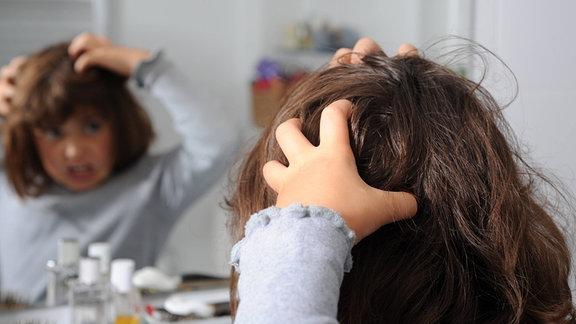 Ein kleines Mädchen steht vor dem Spiegel und kratzt sich mit beiden Händen am Kopf.