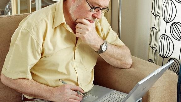 Ein älterer Mann sitzt mit einem Laptop auf einem Sofa